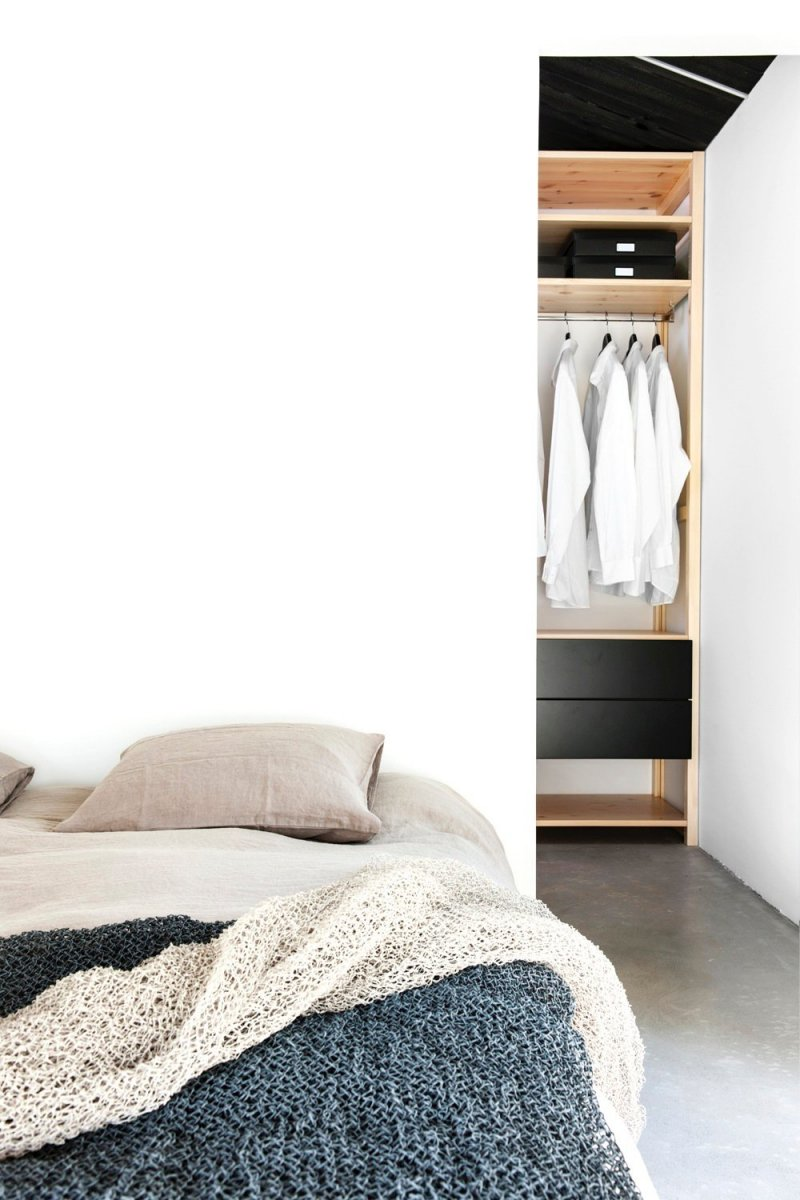 Bedroom with walk-in closet behind bed. Maja by Deko