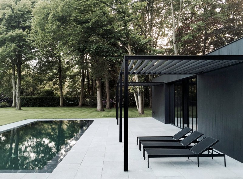 Pool patio with black steel pergola. CD Poolhouse by Marc Merckx