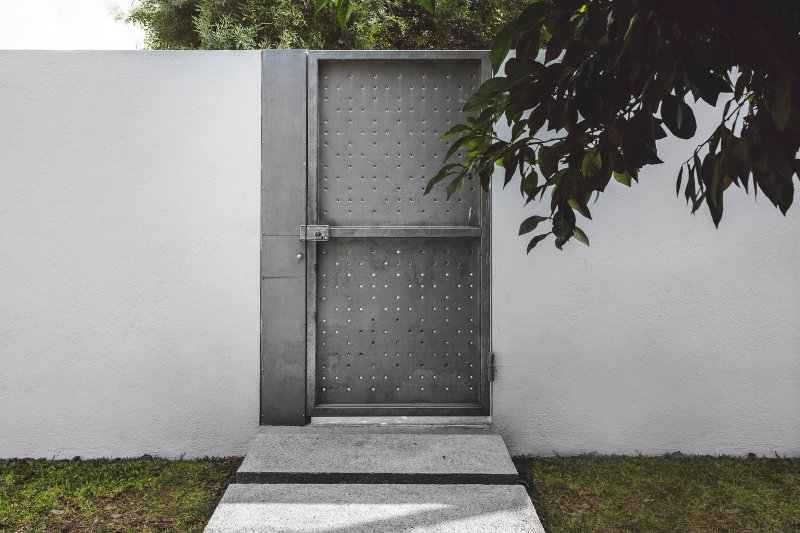 Perforated metal door. Doblado House by Isauro Huizar Studio