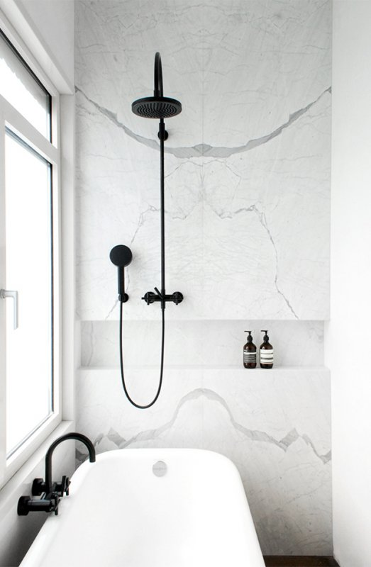Marble wall with black shower fixtures. JVR Apartment by Dieter Vander Velpen Architects