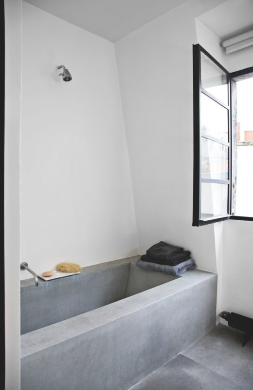 Bathroom with concrete tub. Raw and minimal loft of Trish Deseine