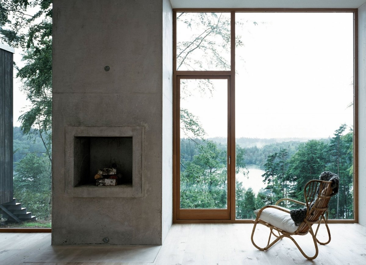Concrete fireplace between large windows. Forester's House and Service Building by Petra Gipp Arkitektur