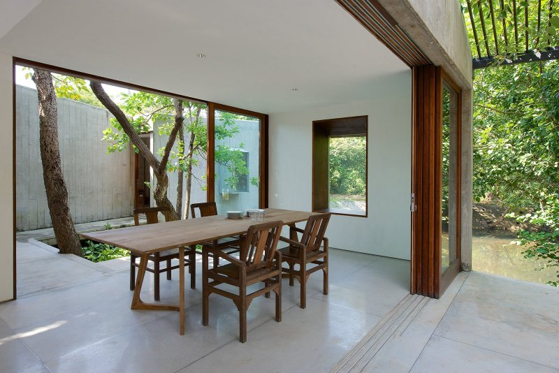 Dining room opens to courtyard. House on a Stream by Architecture BRIO