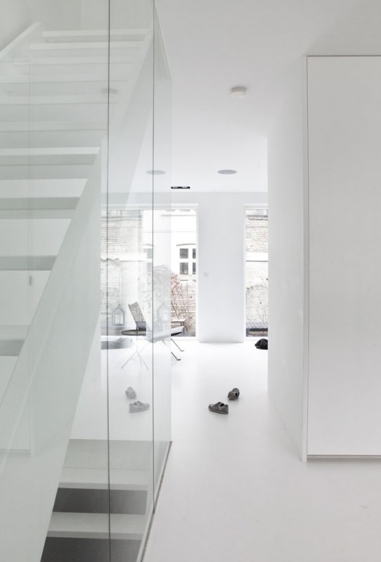 White staircase behind glass wall. Copenhagen Townhouse II by Norm Architects