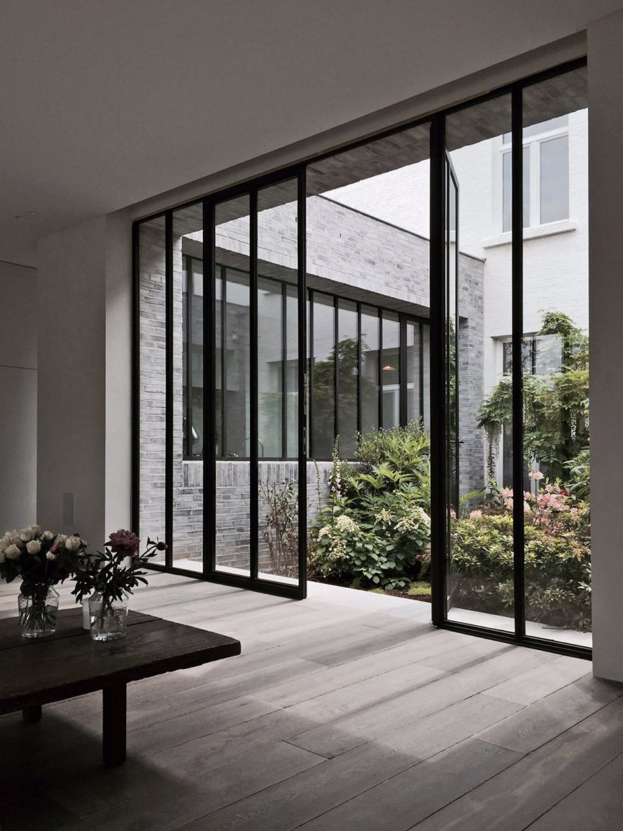 Living area with floor-to-ceiling double glazed door leading out to the garden.